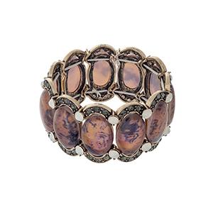 Burnished gold tone stretch bracelet displaying orange oval shaped stones with black diamond and white opal rhinestone accents.