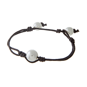 """Brown cord bracelet with a single faux ivory pearl focal. Approximately 8"""" in length."""