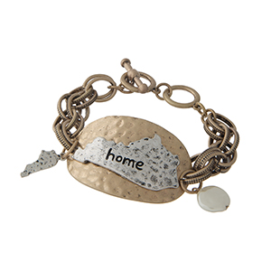 """Burnished gold tone toggle bracelet displaying a hammered plate with a burnished silver tone state of Kentucky stamped """"home"""". Approximately 8"""" in length."""