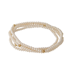 Multiple strand ivory beaded stretch bracelet with gold tone bead accents.