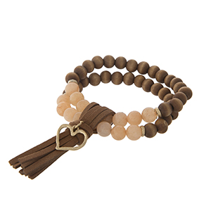 Two strand peach stone and wood bead stretch bracelet with a brown tassel and gold tone heart charm.