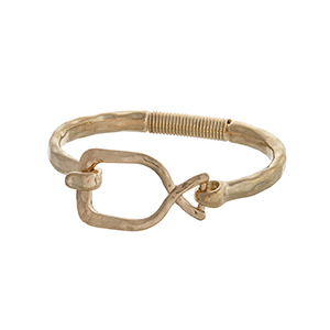 Worn gold tone latch bangle bracelet with an open shape.