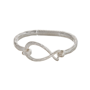 Worn silver tone latch bangle bracelet with an open teardrop.