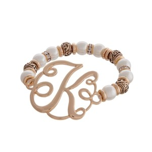 """Gold tone and pearl beaded stretch bracelet featuring the letter """"K"""" initial and accented with clear rhinestones."""