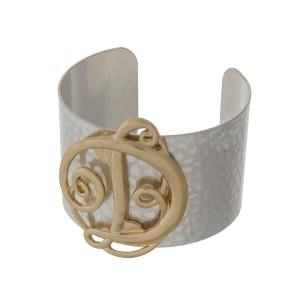 Hammered silver tone cuff bracelet with a gold tone script 'D' initial.
