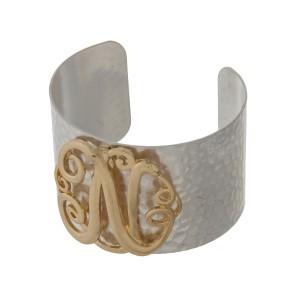 Hammered silver tone cuff bracelet with a gold tone script 'N' initial.