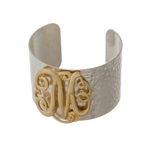 Hammered silver tone cuff bracelet with a gold tone script 'M' initial.