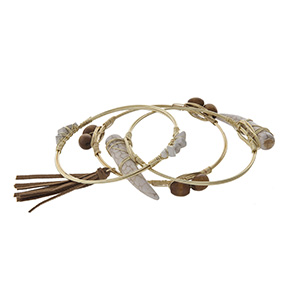 Gold tone wire wrapped bracelet set with brown beads, white chip stones, and ivory horns. Set of three.
