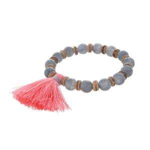 Gray beaded stretch bracelet with wooden accents and a pink tassel.