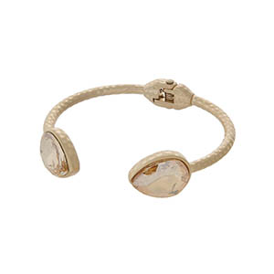 Hammered gold tone cuff bracelet with teardrop topaz stones.