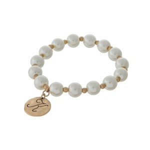Gold tone stretch bracelet with cream pearl beads and a hammered disc stamped with a script 'K' initial.