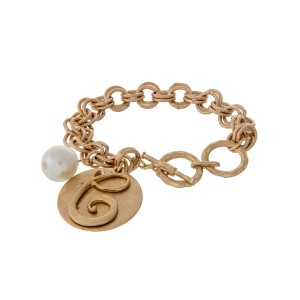 Gold tone toggle bracelet with a script 'C' initial and a pearl bead charm.