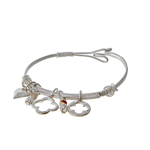 Silver tone bangle bracelet with quatrefoil and heart charms.