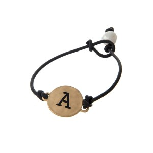 Brown cord bracelet with a gold 'A' stamped disc and a freshwater pearl bead closure.
