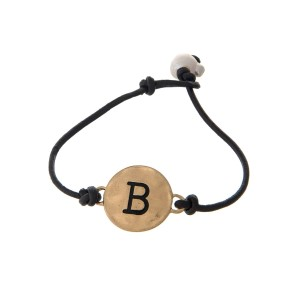 Brown cord bracelet with a gold 'B' stamped disc and a freshwater pearl bead closure.