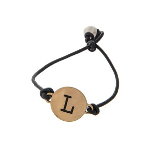 Brown cord bracelet with a gold 'L' stamped disc and a freshwater pearl bead closure.