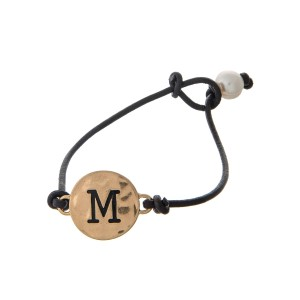 Brown cord bracelet with a gold 'M' stamped disc and a freshwater pearl bead closure.