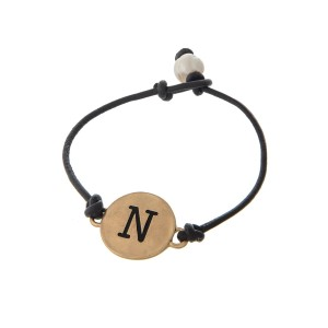 Brown cord bracelet with a gold 'N' stamped disc and a freshwater pearl bead closure.