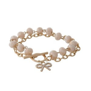 Gold tone toggle bracelet with ivory faceted beads and a bow charm.