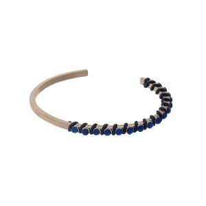 Gold tone cuff bracelet with navy wrapped thread and blue rhinestones.