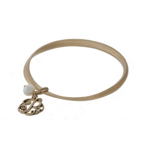 Burnished gold tone twist bangle with a script 'P' initial and freshwater pearl charms.