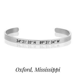 Silver tone cuff bracelet stamped with the coordinates of Oxford, Mississippi.