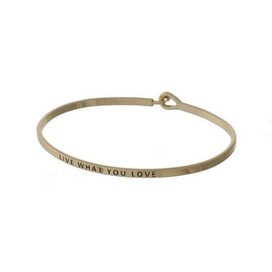 "Gold tone, dainty bangle bracelet stamped with ""Live what you love."""