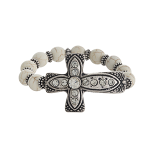 Ivory stretch bracelet with a silver tone cross, accented with clear rhinestones.