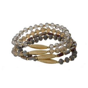 Gray beaded stretch bracelet set with gold tone accents.