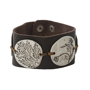 Brown leather snap bracelet with silver tone circles, stamped with leaf shapes.