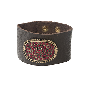 Brown leather snap bracelet with a gold tone and red rhinestone pave focal.