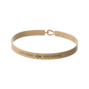 "Gold tone, brass bangle bracelet stamped with ""Just Focus, Keep Aiming."""
