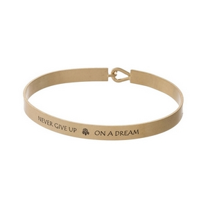 "Gold tone, brass bangle bracelet stamped with ""Never Give Up On A Dream."""