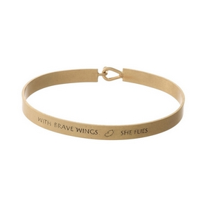 """Gold tone, brass bangle bracelet stamped with """"With Brave Wings, She Flies."""""""