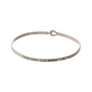 "Silver tone, brass bangle bracelet stamped with ""Think Less, Live More."""