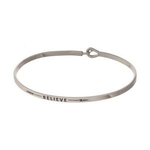 "Silver tone, brass bangle bracelet stamped with ""Believe."""