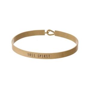 "Gold tone, brass bangle bracelet stamped with ""Free Spirit."""