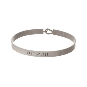 "Silver tone, brass bangle bracelet stamped with ""Free Spirit."""