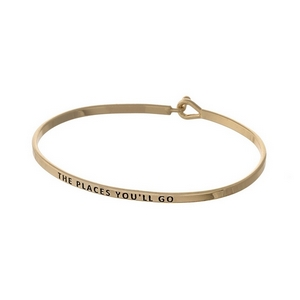 "Gold tone, brass bangle bracelet stamped with ""The Places You'll Go."""