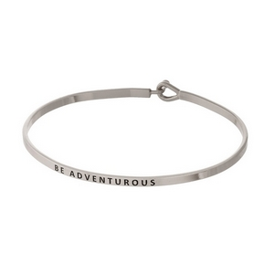 "Silver tone, brass bangle bracelet stamped with ""Be Adventurous."""