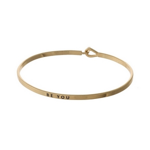 "Silver tone, brass bangle bracelet stamped with ""Be You."""