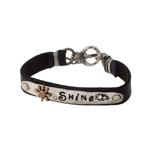 "Black and silver tone faux leather bracelet stamped with ""Shine."""