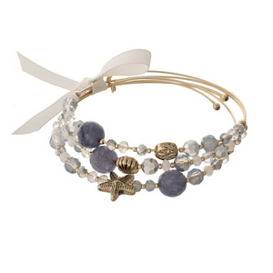 Gold tone cuff bracelet set with gray beads and sea life charms.