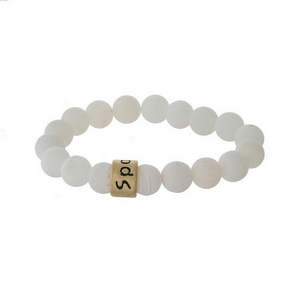 "Matte white, natural stone beaded stretch bracelet with a gold tone bead, stamped with ""Sparkle."""