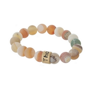 """Matte peach, natural stone beaded stretch bracelet with a gold tone bead, stamped with """"Thankful."""""""
