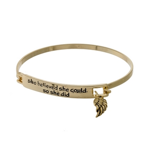 "Gold tone bangle bracelet stamped with ""She believed she could, so she did"" and accented with a wing charm."