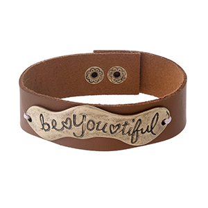 "Camel brown faux leather snap bracelet with a gold tone focal stamped with ""Be You Tiful."" Approximately 1"" in width."