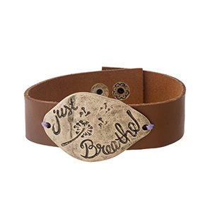"""Camel brown faux leather snap bracelet with a gold tone focal stamped with """"Just Breathe."""" Approximately 1"""" in width."""
