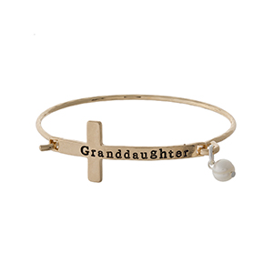"Gold tone bangle bracelet with a cross focal, stamped with ""Granddaughter"" and accented with a pearl bead."