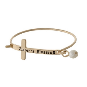"Gold tone bangle bracelet with a cross focal, stamped with ""Sister's Blessing"" and accented with a pearl bead."